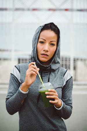 nutritive: Tough looking urban sporty woman taking a rest for drinking nutritive detox smoothie. Fitness nutrition and outdoor workout concept.