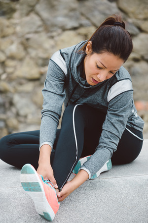 Fitness woman suffering painful ankle sprain injury after running or working out.