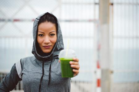 Donna di successo urbano sportiva di prendere una pausa per bere nutritivo frullato di disintossicazione. Fitness Nutrition e il concetto stile di vita sano. Archivio Fotografico - 48966642