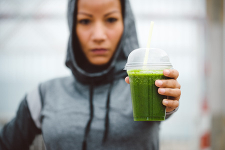 Fitness diet and nutrition concept. Tough looking urban sporty woman taking a rest for drinking nutritive detox smoothie. Foto de archivo