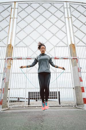 jumping: Aptitud de la mujer urbana haciendo saltar la cuerda ejercicio al aire libre. Atleta femenina Salto deportivo para el entrenamiento corporal. Foto de archivo