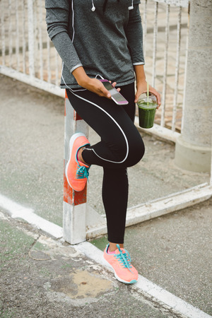 a workout: Urban fitness lifestyle and sportswear concept. Sporty woman holding detox drink and smartphone while taking a workout rest. Stock Photo