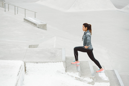 female athlete: Leg lunges exercise on stairs. Fitness woman working out on urban park.