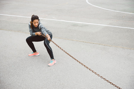 outdoor training: Fitness woman training strength. Strong female athlete pulling a chain for outdoor urban workout. Stock Photo