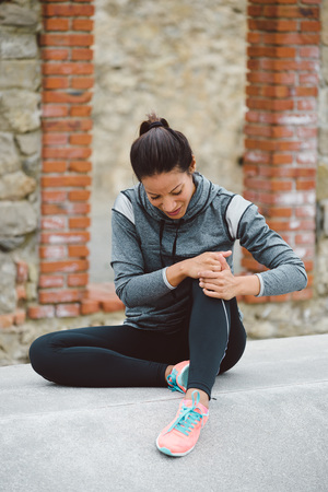 dolor: Fitness mujer que sufre una lesión de rodilla o dolor de rodilla después de correr o hacer ejercicio. Foto de archivo