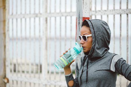 ethnic woman: Tough looking urban fitness woman taking a rest for drinking water.  Sporty ethnic athlete wearing sunglasses and hood for outdoor workout.