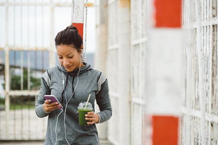 alimentacion: Fitness mujer que toma un descanso del entrenamiento para los mensajes de texto en su teléfono inteligente, mientras que beber un batido de desintoxicación nutritiva y escuchar música. estilo de vida moderno sana y el deporte concepto. Foto de archivo