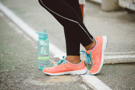 running shoes: Urban fitness lifestyle and sportswear concept. Sport running shoes and bottle of water close up.