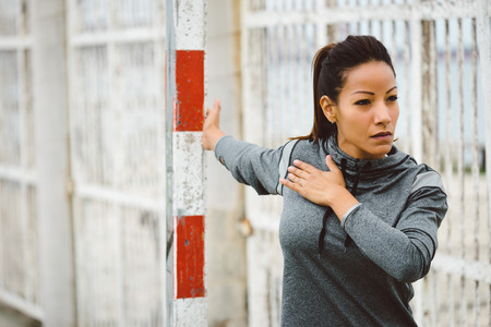 Fitness woman doing chest stretching exercise. Female motivated athlete working out and warming up outdoor. Healthy and sport lifestyle concept.