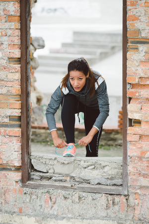 'getting ready': Female fitness athlete getting ready for running or outdoor urban workout. Sporty woman lacing sport shoes. Motivation for working out concept.