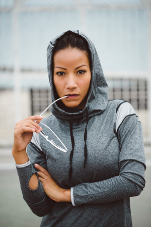 tough woman: Tough looking fitness woman portrait. Sporty urban ethnic athlete wearing sunglasses and hood for outdoor workout. Stock Photo