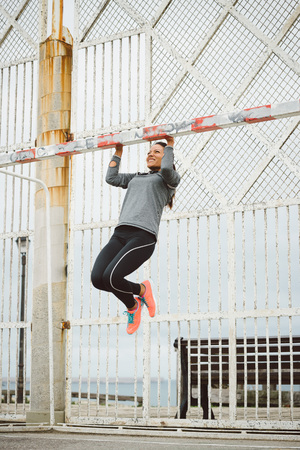 Fitness woman doing pull ups strength workout. Female athlete training back and arm muscles outdoor. Banque d'images