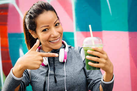 recommending: Successful fitness urban woman taking a rest for drinking and recommending detox smoothie. Healthy nutrition and lifestyle concept.