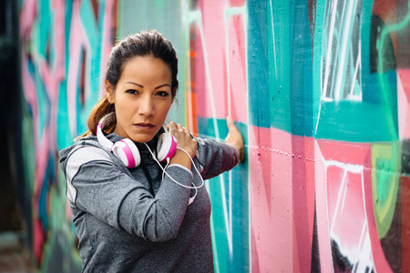 ethnic woman: Sporty woman stretching arm and chest outdoor. Outdoor urban workout and healthy fitness lifestyle concept.