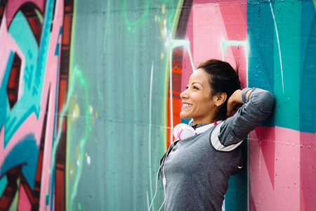 tranquility: Successful urban fitness woman taking a rest for relaxing. Tranquility, workout success and joyful healthy lifestyle concept.