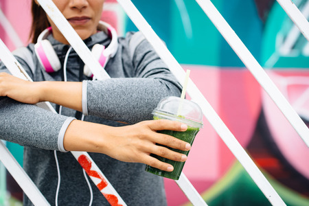 Fitness lifestyle and nutrition concept. Sporty woman holding green detox smoothie drink. Female athlete resting on urban outdoor workout break. photo