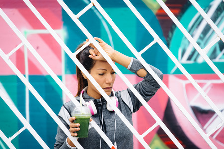 Tired fitness urban woman taking a rest for drinking detox smoothie. Healthy nutrition and lifestyle concept. Downcast ethnic female athlete portrait. photo