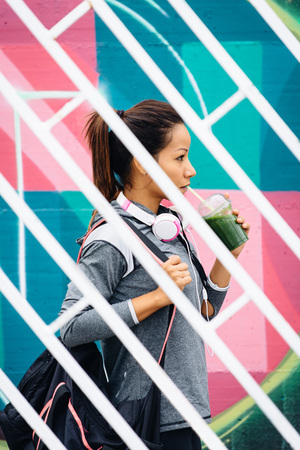 Urban fitness woman drinking detox smoothie while going to the gym. Female athlete walking on street wearing headphones and sportswear. photo