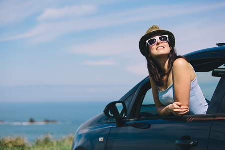 Relaxed happy woman on summer roadtrip travel vacation leaning out car window on blue sky background.