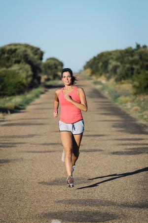 mujer deportista: Motivado deportivo mujer que se ejecutan en la carretera de asfalto país. Femenino al aire libre entrenamiento de un atleta. Foto de archivo