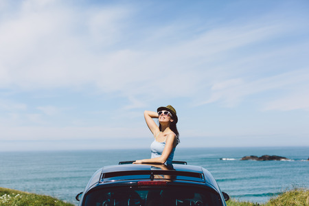 sunroof: Joyful happy woman on summer travel vacation to the coast  leaning out car sunroof towards the sea and sky.