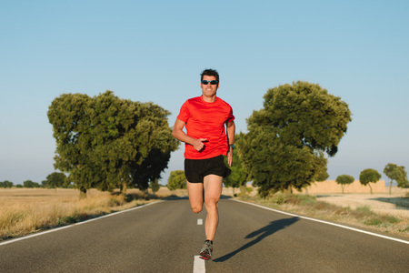 Fit man running on country road. Male athlete training outdoor for marathon and endurance. Stock Photo