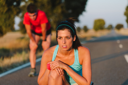 sweaty: Sweaty athletes taking a rest after road running race or marathon. Tired female runner and man resting and breathing. Sport motivation and lifestyle concept.