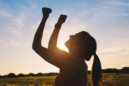 Woman raising arms for celebrating fitness outdoor workout success. Motivation and healthy lifestyle goals concept.