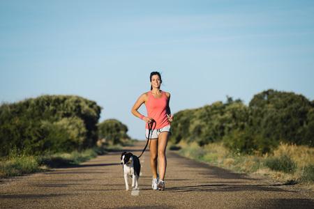 Donna sportiva e cane insieme in esecuzione su strada di campagna d'estate il tramonto. Allegro formazione atleta di sesso femminile e l'esercizio all'aperto con il suo animale domestico. Archivio Fotografico - 52160104