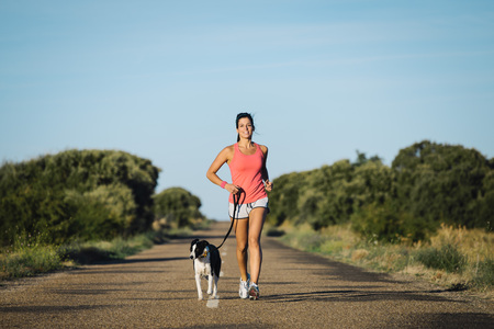 pets: Sporty woman and dog running together on country road on summer sunset. Cheerful female athlete training and exercising outdoor with her pet.