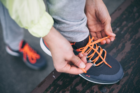 lacing sneakers: Woman lacing sport shoes before running or fitness workout.