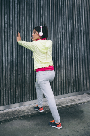 calf: Urban fitness woman stretching legs and calves. Sporty girl with headphones working out outside.