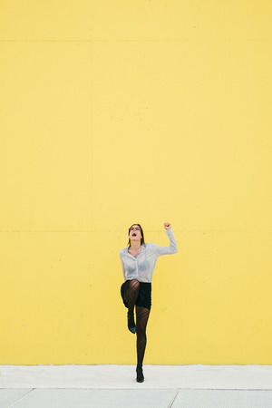 proffesional: Happy proffesional woman celebrating business or job success against yellow wall. Trendy stylish modern businesswoman. Stock Photo