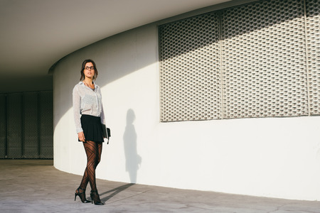 secretary skirt: Fashionable female entrepreneur or professional business woman walking outside. Modern businesswoman wearing stylish clothes and glasses.