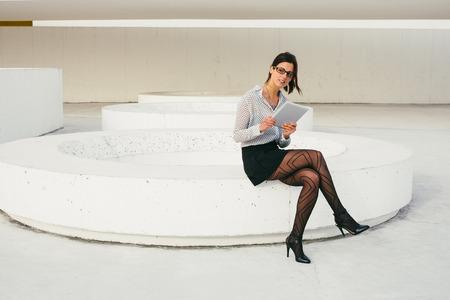 secretaries: Mujer moderna del profesional de la lectura en la tabla fuera del edificio de oficinas. Moda joven negocios haciendo su trabajo en un descanso.