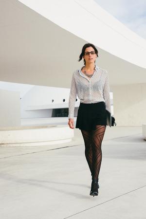 skirts: empresario de moda femenina o mujer de negocios profesional caminar por la calle. de negocios moderno que desgasta la ropa con estilo y gafas.