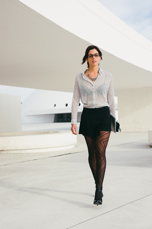 tights: Fashionable female entrepreneur or professional business woman walking outside. Modern businesswoman wearing stylish clothes and glasses.