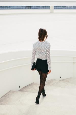 bajando escaleras: Mujer profesional bajando escaleras. Vista posterior de la mujer de negocios moderna con estilo que lleva el bolso y la tableta.