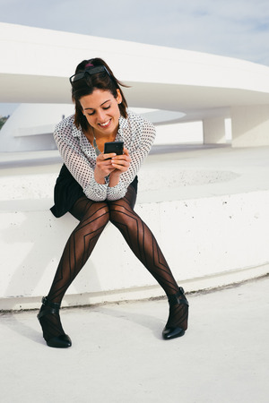 sexy secretary: Cheerful stylish business woman texting or reading message on smartphone and sitting outside from modern corporate building. Relaxed young sexy businesswoman on a job rest.