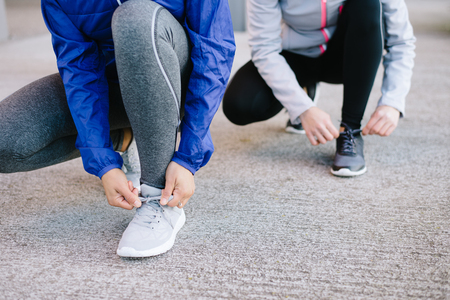 'getting ready': Women lacing sport shoes and getting ready for urban running.