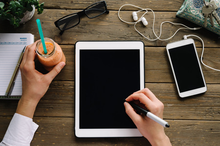 touchpad: Woman drawing on tablet with pen stylus. Entrepreneur using touchpad on wooden desk with smartphone and detox smoothie drink.