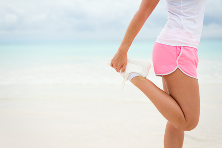 Running and fitness exercising lifestyle on summer concept. Woman stretching legs before working out towards the sea.