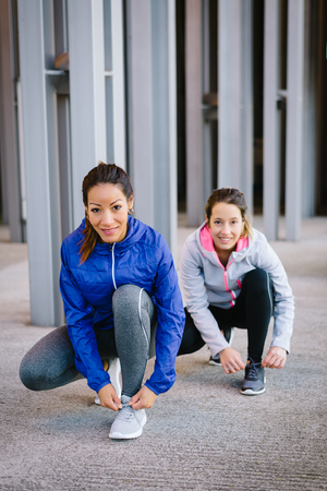 lacing sneakers: Two female athletes ready for urban running. Women getting ready for fitness workout and exercising.