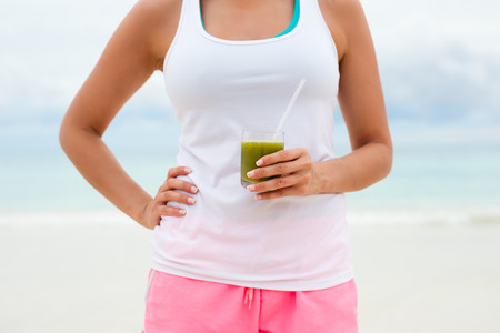 summer diet: Fitness woman holding green healthy detox smoothie. Summer diet and nutrition for slim down concept.