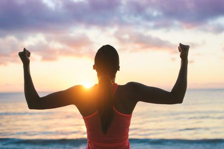 Femme de fitness célébrant le succès de l'entraînement physique et la motivation vers la mer et le coucher du soleil.