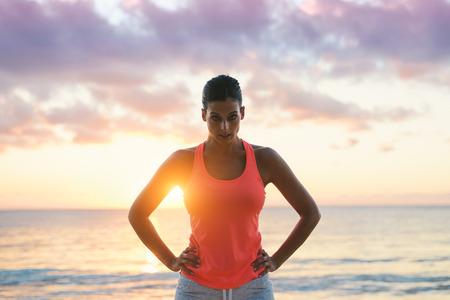 Aptitud de la mujer motivación. Desafiante y motivador en busca de la mujer atleta con el sol y el mar detrás.