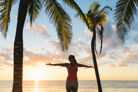 outstretching: Blissful fitness woman enjoying outdoor summer sunrise or sunset workout at the beach. Happy female athlete exercising during vacation under tropical palms at Riviera Maya, Mexico. Stock Photo