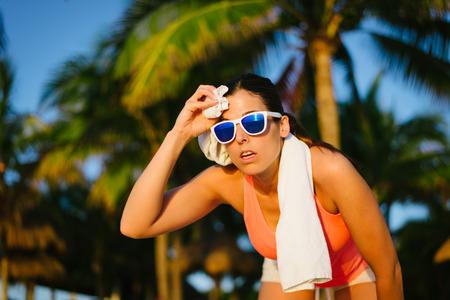 cansancio: Mujer cansada de la aptitud que limpia el sudor de la frente con una toalla después del entrenamiento playa de verano.