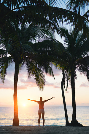 outstretching: Blissful fitness woman enjoying outdoor summer relaxing sunrise or sunset at the beach after workout. Happy female athlete exercising during vacation under tropical palms at Riviera Maya, Mexico. Stock Photo