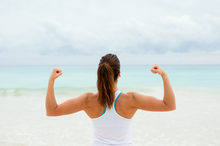 Strong fitness woman showing arms biceps towards the sea. Healthy lifestyle motivation and success.